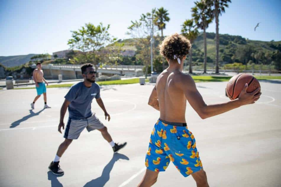 Basketball player with duck shorts and no shirt looks to get by his defender at the park.