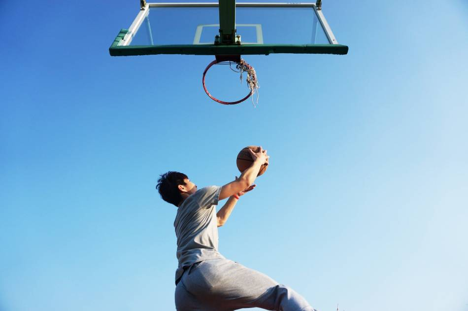 Basketball player in grey lays up the ball from beneath the basket at the park.