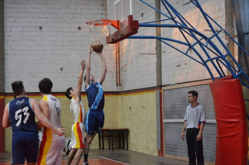 Basketball player in blue makes it past the player in white to layup the ball.