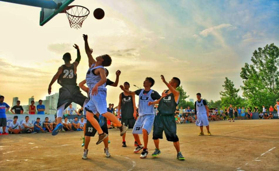 Youth basketball player has his shot blocked in an outdoor game.