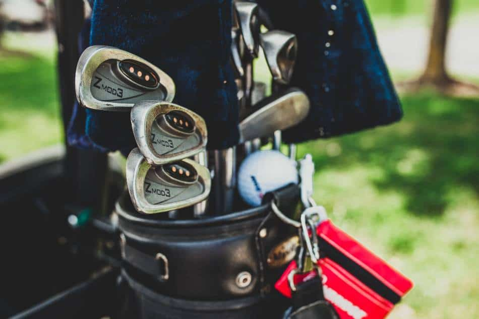 Zoomed in view of a set of golf clubs in the bag.