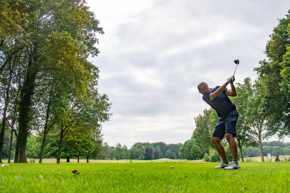 Golfer in a polo and shorts prepares to tee off with his driver.