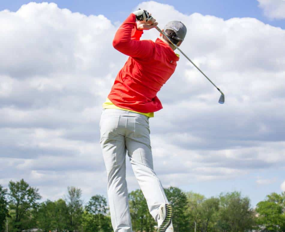 Golfer in red watches a shot he took with his iron.