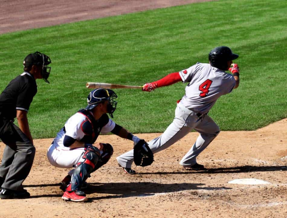 Baseball player wearing the number 4 swings and puts the ball in play.