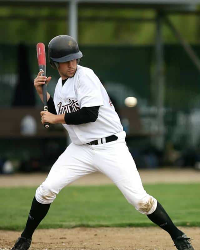 Baseball batter in white braces himself to get hit by a pitch.