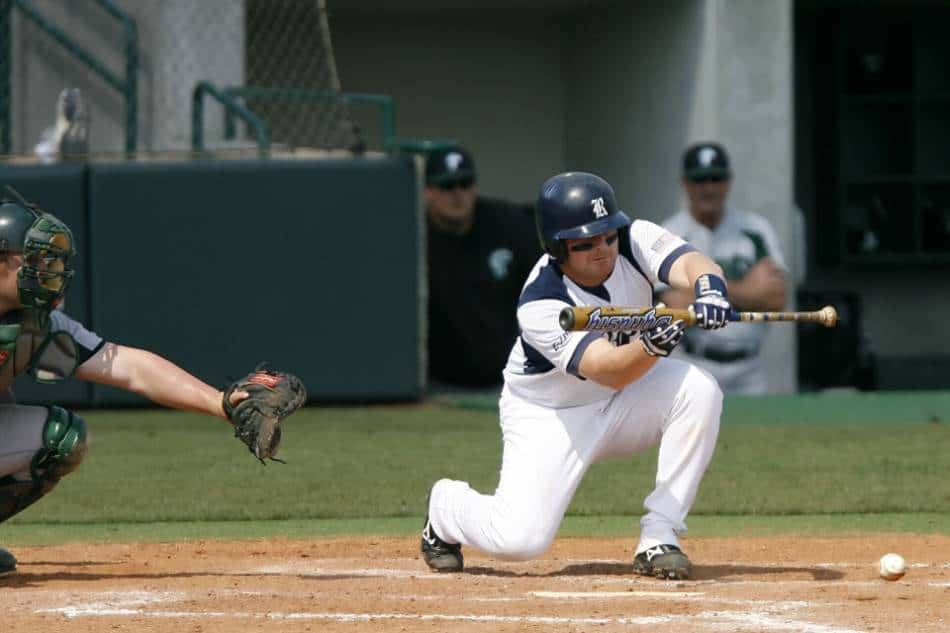 A college baseball player in white lays down a bunt with a yellow aluminum baseball bat.