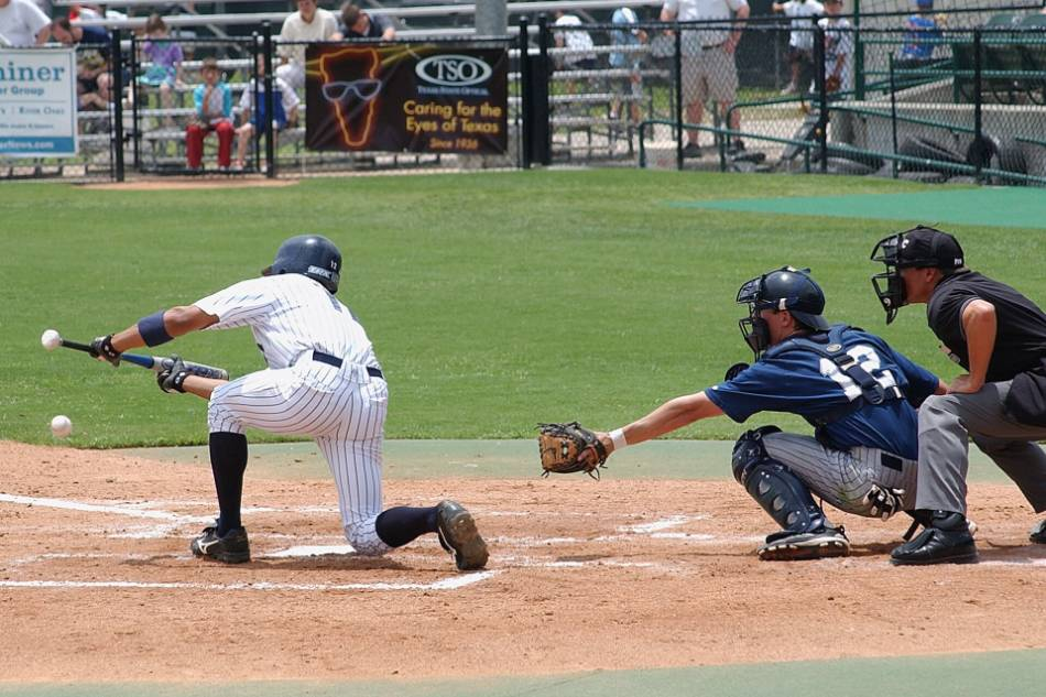 A baseball player in pinstripes successfully lays a bunt down the first base line.