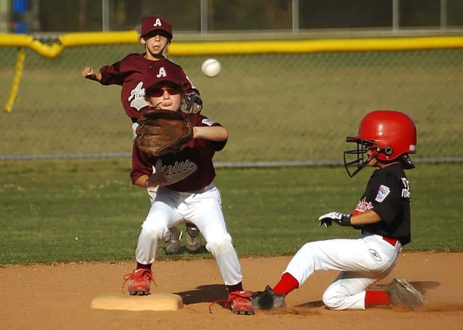 A little league baseball player in maroon prepares to get the runner in blue out on a fielder's choice.