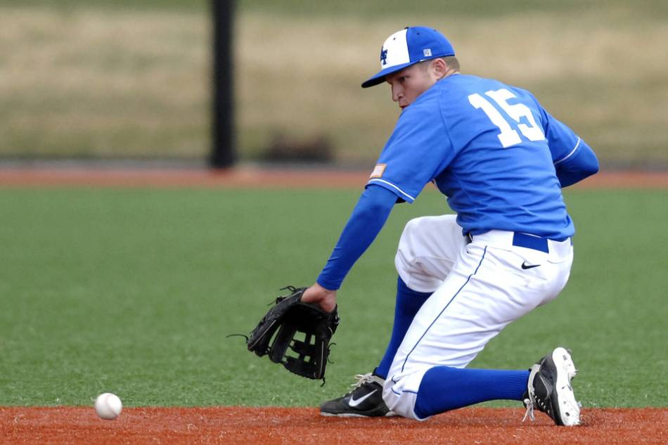 A college baseball player player in blue and white prepares to backhand a groundball.