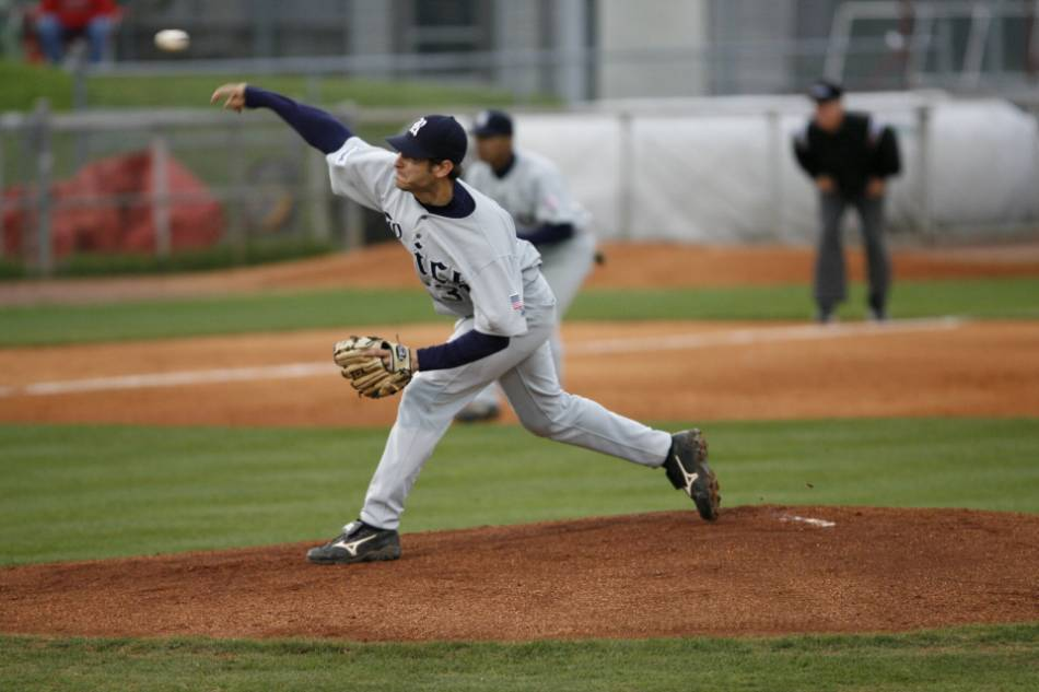 College baseball pitcher in grey and navy throws the ball home.