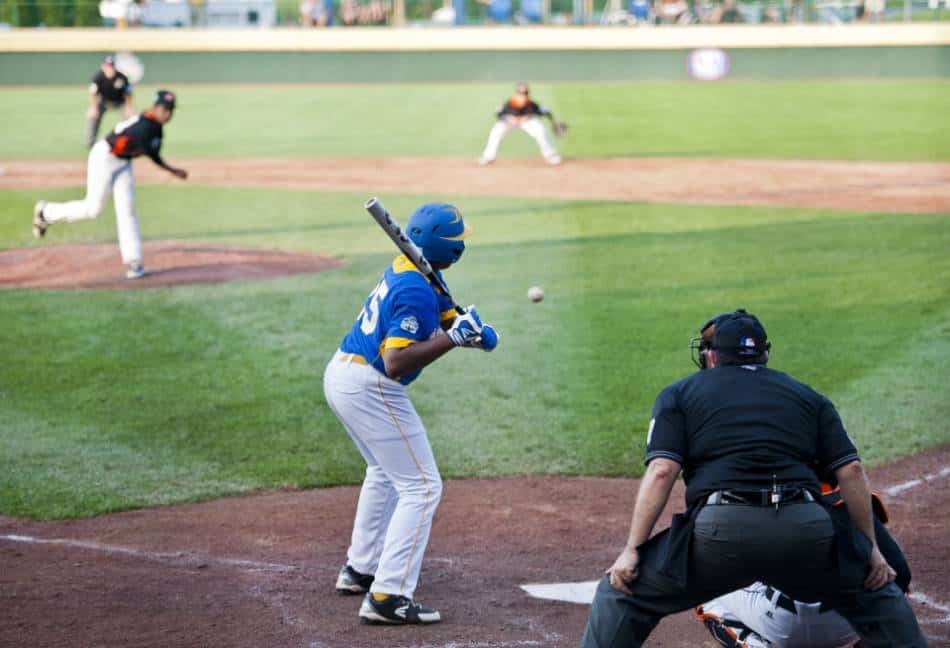 Little League baseball player in blue and yellow stands in the batter's box as the pitch goes by.