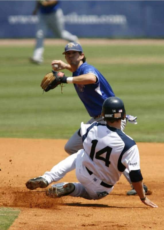 College baseball player in blue tries to turn a double play as the player in white slides into second base.