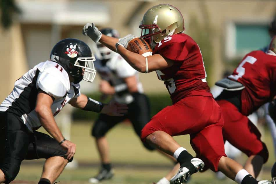 Football running back in red and gold tries to get past the defender in white and black.
