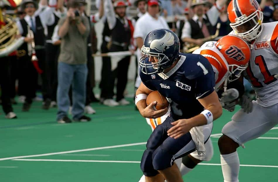 Player in blue with the football  evades two defenders in white and orange.
