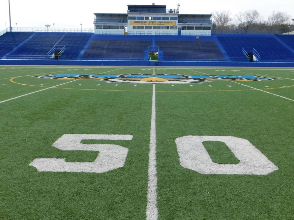 On field view of a football stadium from the 50-yard line.