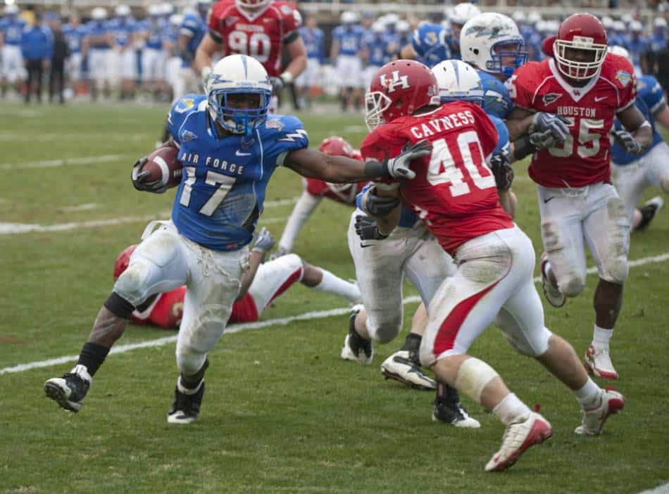 Air Force college football player tries  to run the ball up the sideline.