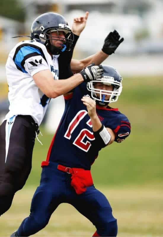 Highschool football player in white and blue commits defensive pass interference.