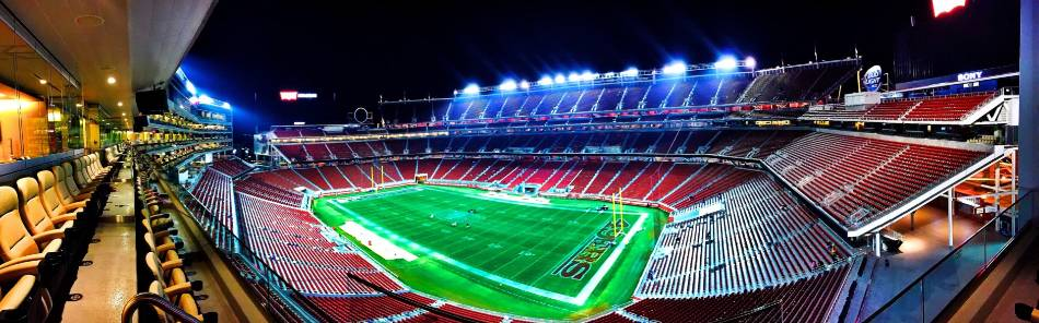 Aerial view of the 49ers Candlestick Park with the lights on at night.
