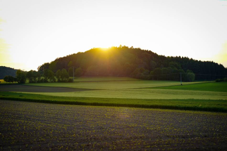 Sun setting behind a hill, overlooking a golf course.