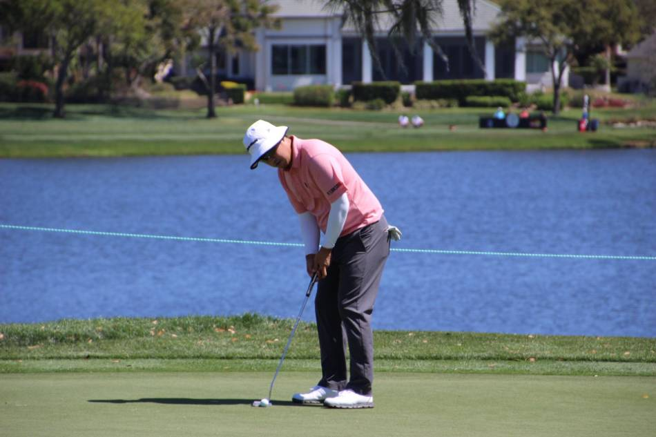 Golfer in a pink polo and white hat attempts to putt the ball in the hole.