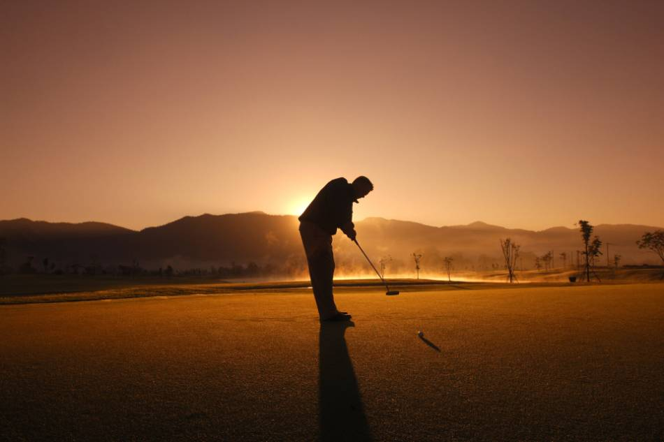 Golfer putting on the green as the sun sets behind him.