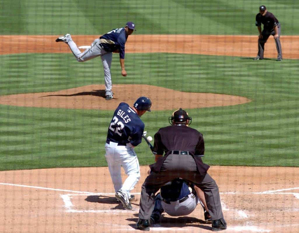 A Milwaukee Brewers pitcher throws a pitch in the strike zone that the batter swings at.
