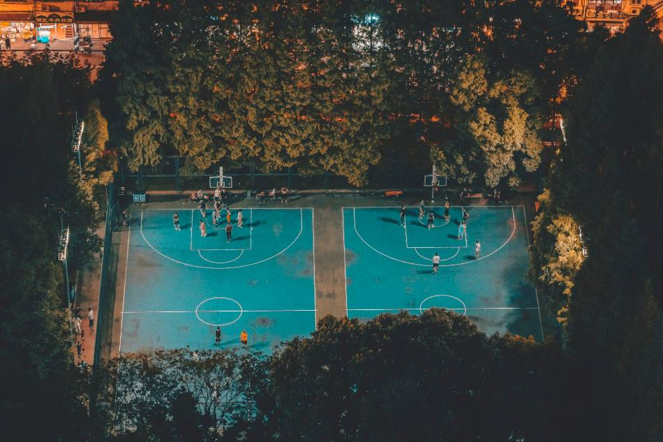 Two outdoor basketball games going on at night under lights.