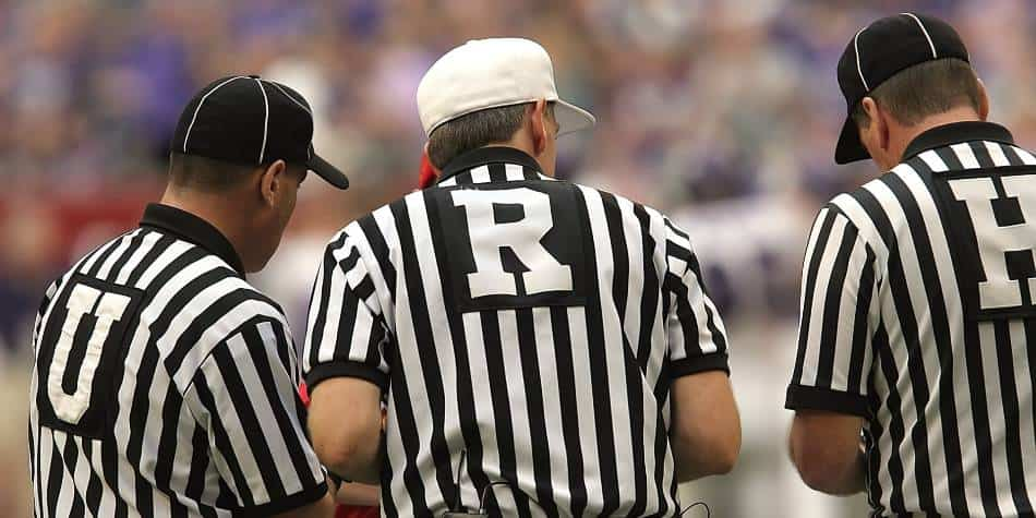 Football referees huddle to go over a call.