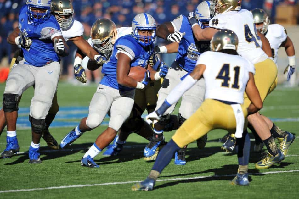 Running back in blue tries to run past a defender in white and gold.
