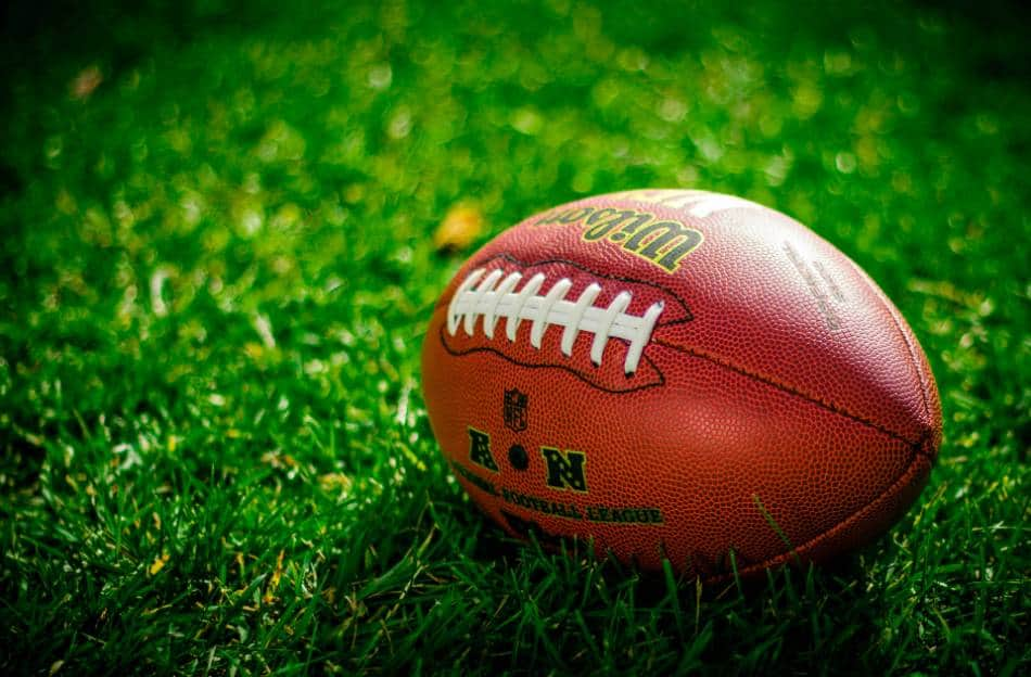 A football sitting on a patch of grass.