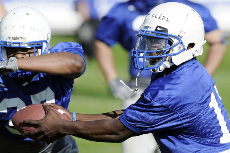 Quarterback in blue and white hands off the ball to his teammate.