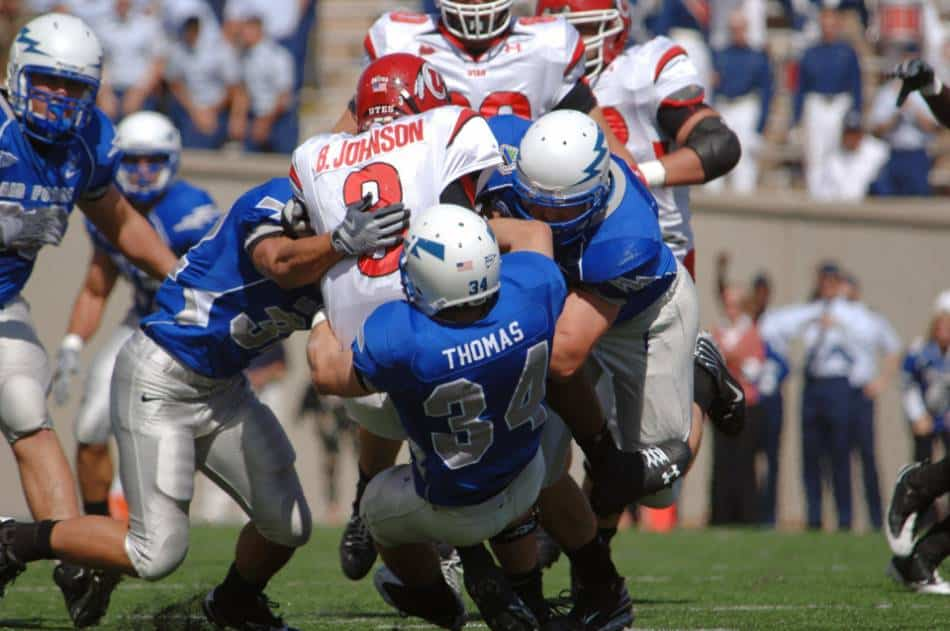 Utah Utes quarterback gets tackled by three players in blue.