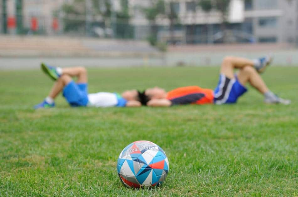 Soccer ball sitting on a patch of grass, with two people lying down head-to-head in the background.