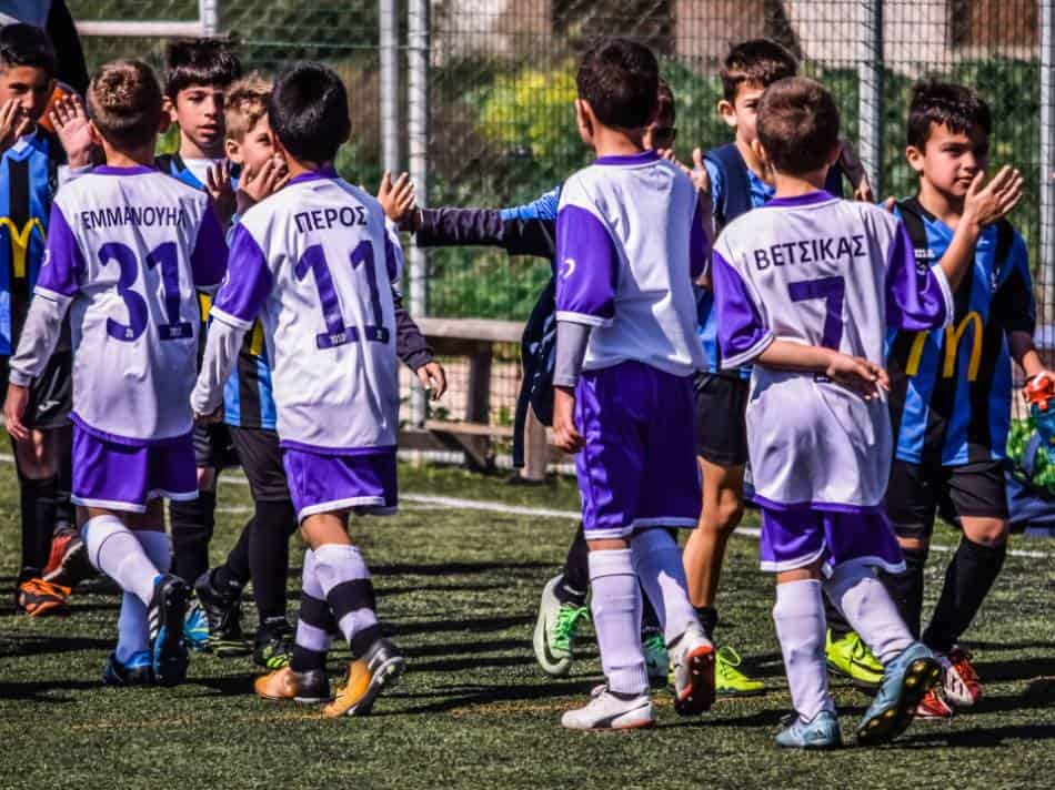 Youth soccer teams high five each other after a game.