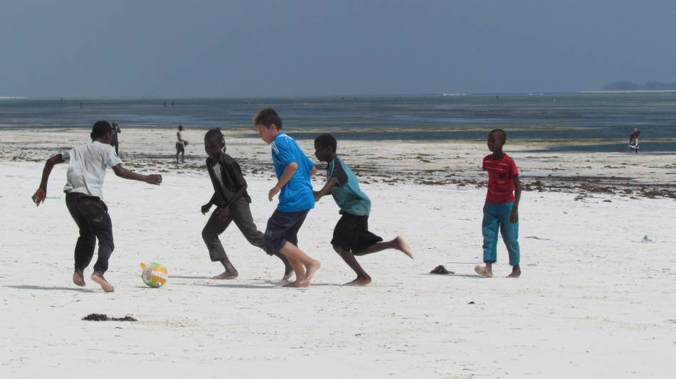 Five kids playing soccer on the beach.