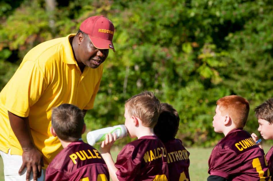 Football coach in yellow and red talks to his players sitting on the bench.