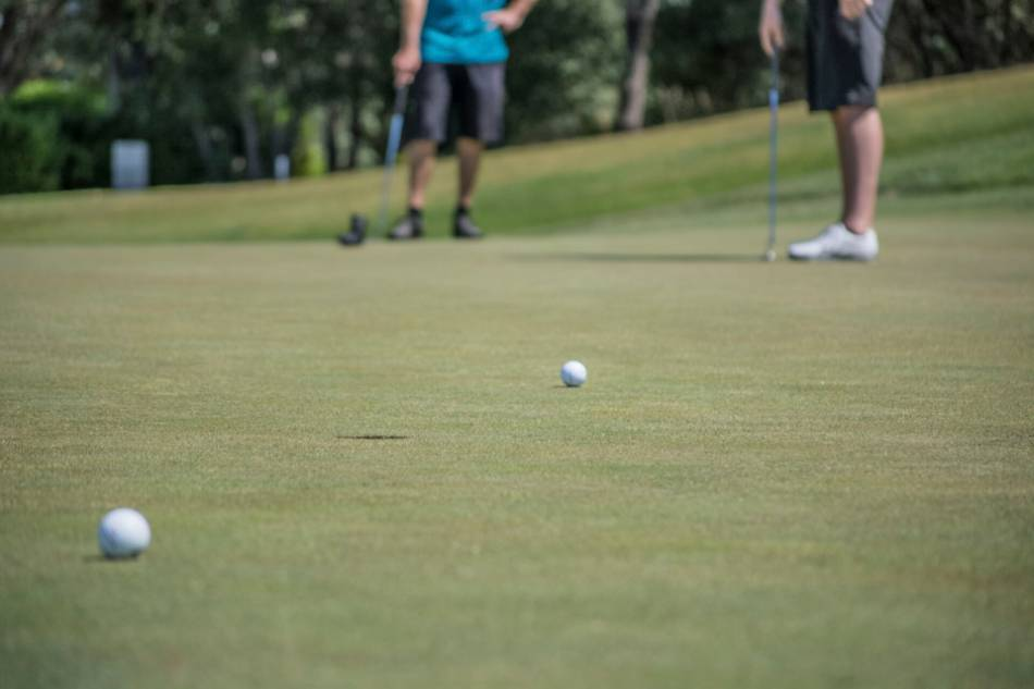 Two golfers prepare to putt their balls into the hole.