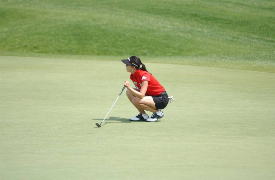 A golfer crouches down to judge how to take her next shot.