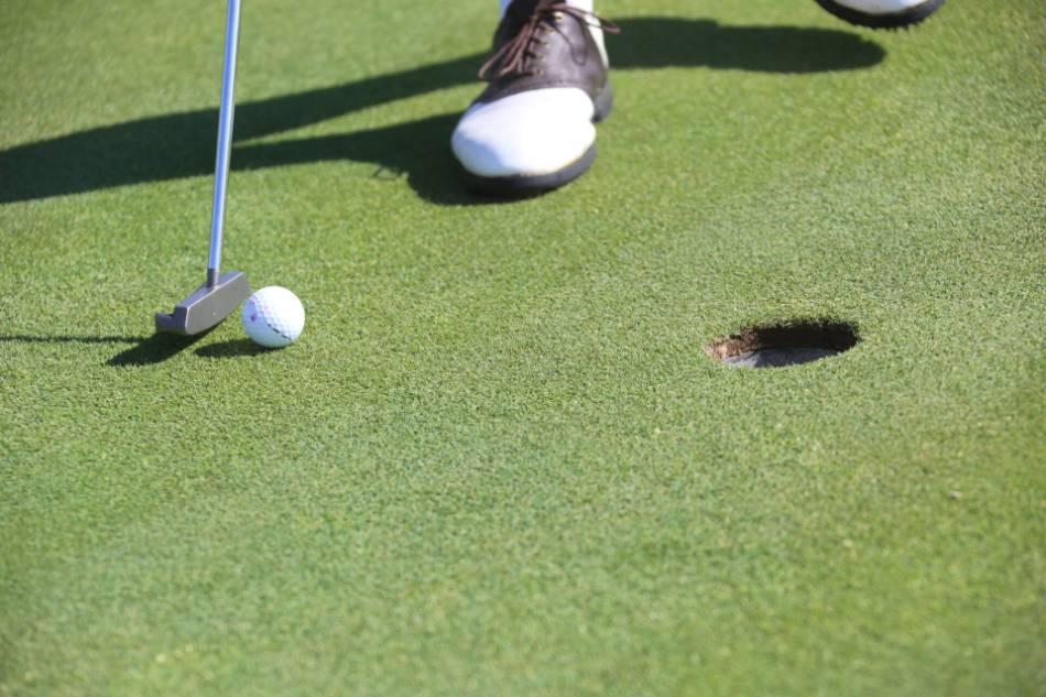 Golfer lines up for a short putt.