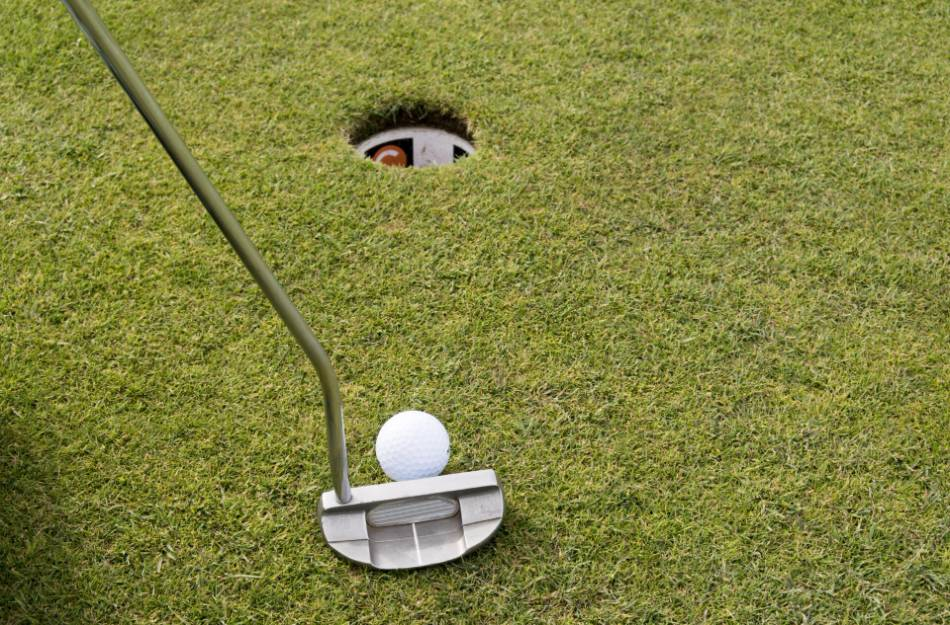 Golfer prepares to putt the ball in the hole.