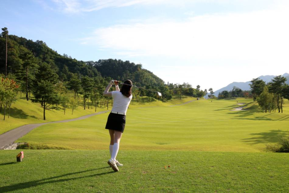 A female golfer tees off with her driver.