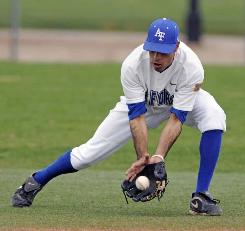 A college baseball player fields a groundball just outside the infield.