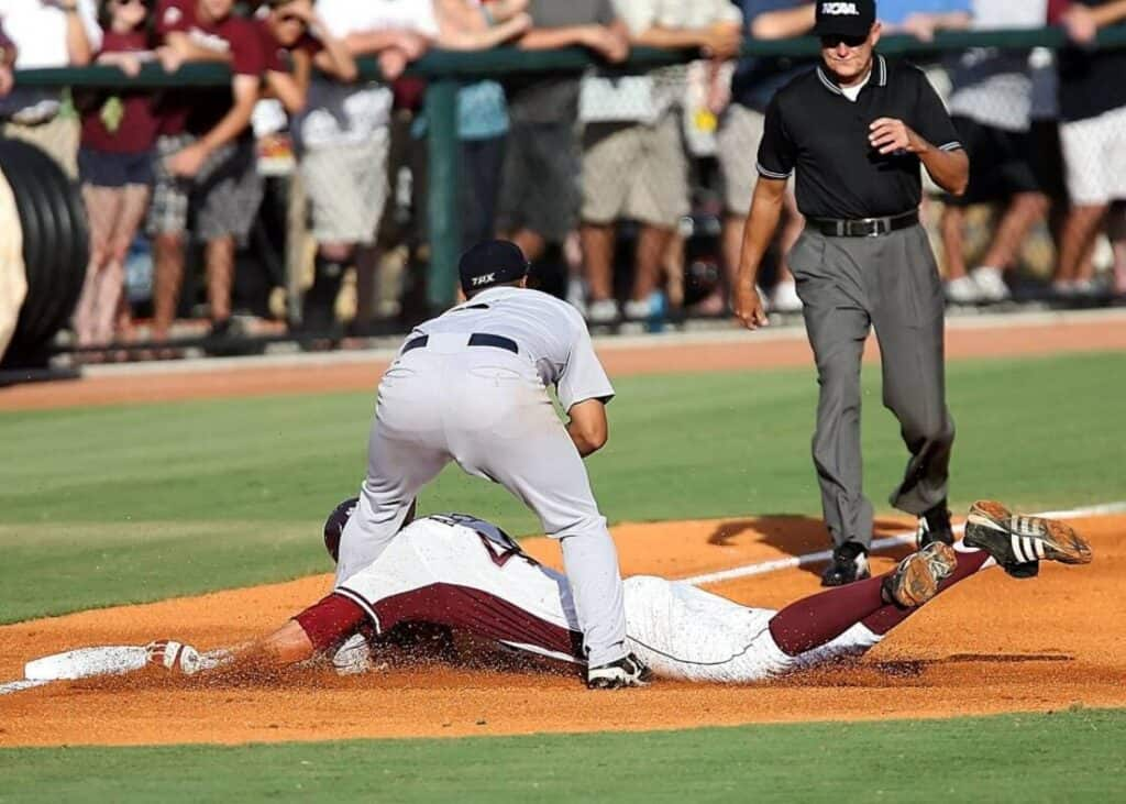 College baseball player gets tagged out, while trying to slide into third base.
