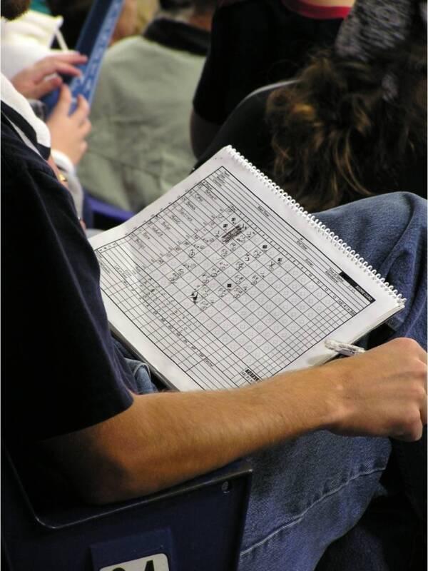 A man keeps score in a scorebook at a baseball game.