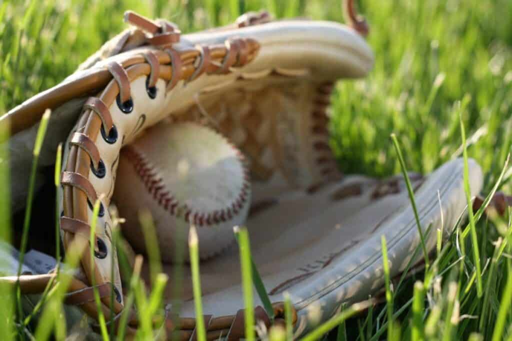 A baseball sits in a glove on the grass.