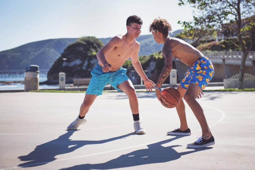 Two basketball players playing basketball outside near the ocean.