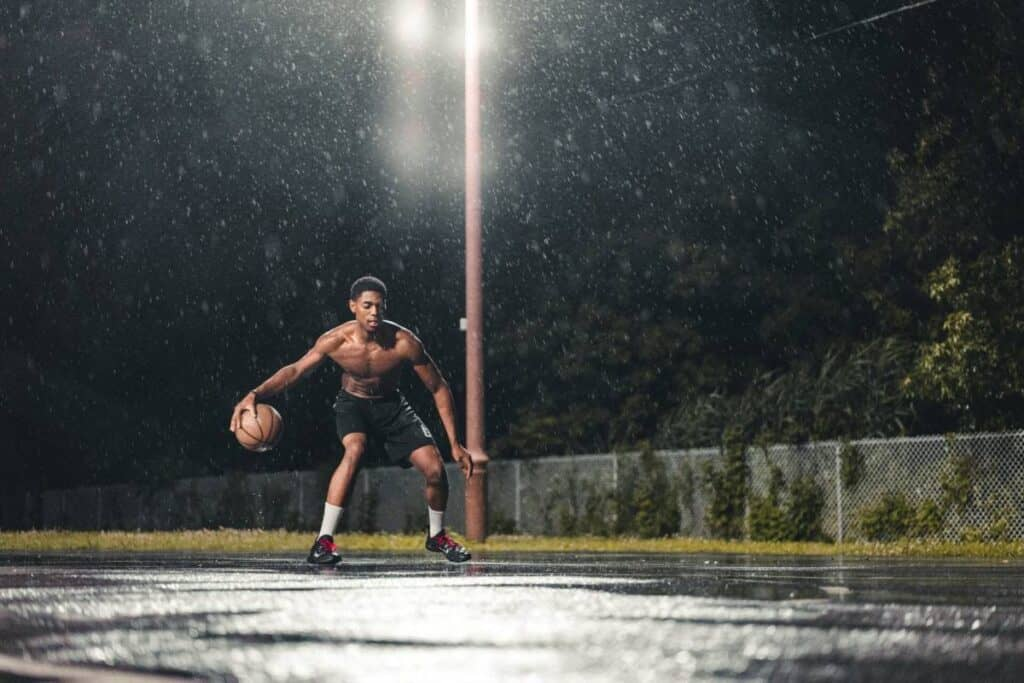 A basketball player practicing their moves in the rain.