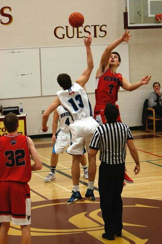 Two high school basketball players participate in a jump ball.