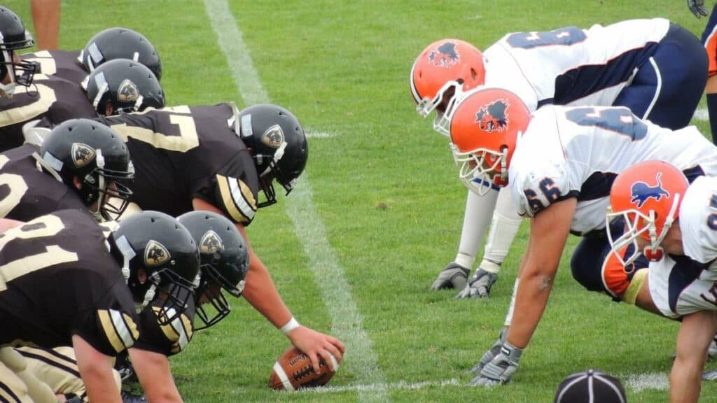 Football players from both teams line up and wait for the center to snap the ball.