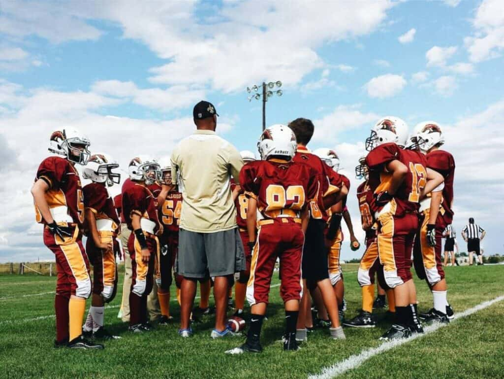 A coach huddles around with his youth football team.
